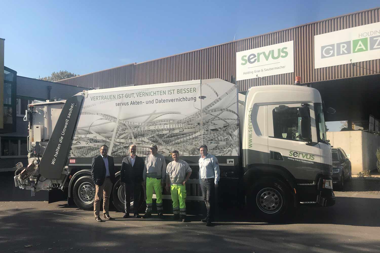 Servus Mitarbeiter vor einem neuen LKW